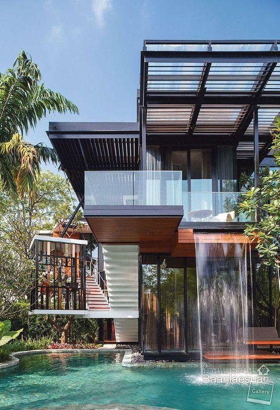 fachada de mucho vidrio con madera y cascada